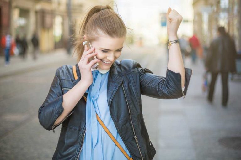 woman with fist in the air celebrating accomplishing customer goodwill fraud