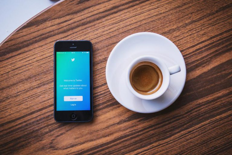 cup of coffee next to phone showing twitter login as example of what is social relationship management all about