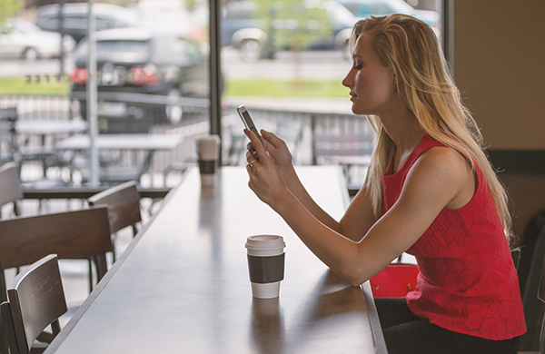 woman using smartphone at coffee shop table