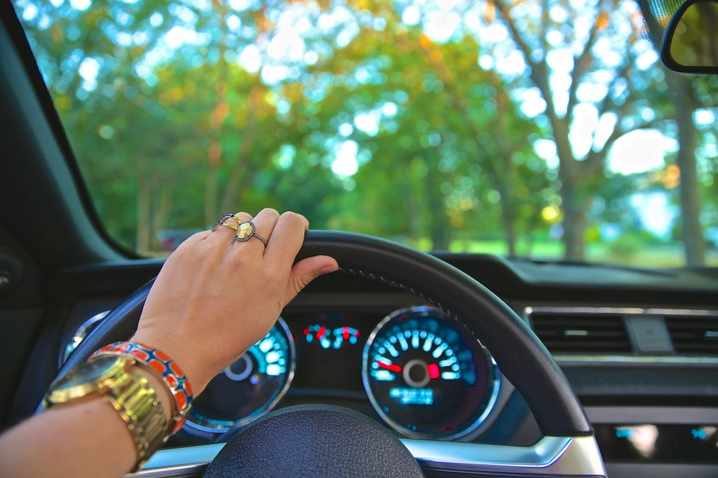 woman with hand on car steering wheel