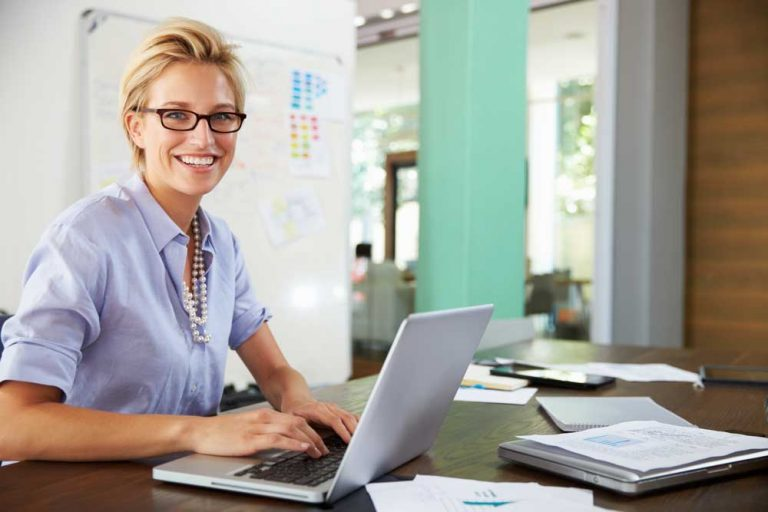 Woman working from home using laptop and wearing headset