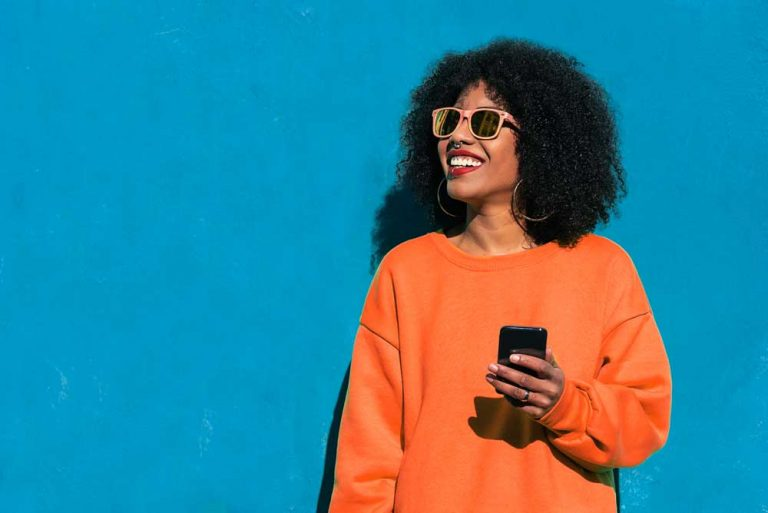 smiling woman using smartphone to engage with customer service automation