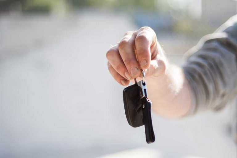Person holding out car keys as part of the car buying customer journey
