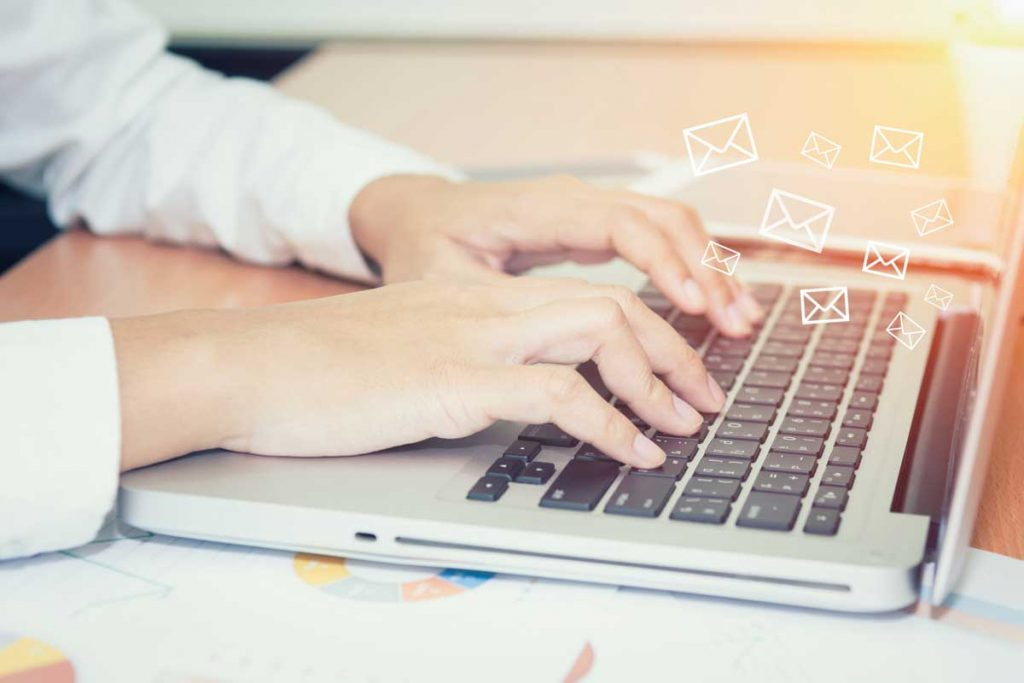 hands typing on laptop with email icon showing email automation