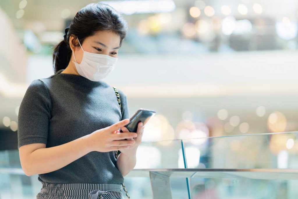 masked customer looking at phone showing how businesses use AI to provide immediate answers across devices